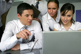 Curious businesspeople looking at a laptop — Stock Photo