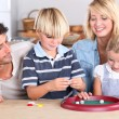 Family playing game at kitchen table — Stock Photo