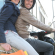 Friends on a scooter after shopping — Stock Photo