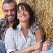 Couple of farmers all smiles posing in barn — Stock Photo