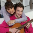 Young couple playing a guitar at home — Stock Photo #9050987