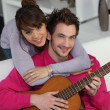 Young couple playing a guitar at home - Stock Photo