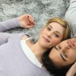Young couple lying top to tail on a grey carpet — Stock Photo