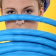 Female construction worker peeking through corrugated tubes — Stock Photo #9051210