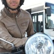 Man on a moped with a bus in the background — Stok fotoğraf