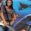Stock Photo: Female guitarist stood by graffiti