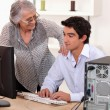 Stock Photo: Mhelping elderly womwith computer problems