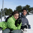 Young couple sat in snow - Stock Photo
