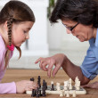 Stock Photo: Young girl playing chess with grandma