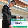 """Realty agent leaning on """"House for sale"""" sign — Stock Photo"""