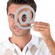 Man holding metallic at symbol over eye — Stock Photo