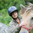 Child caressing horse — Stock fotografie #9053859