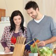 Young couple looking at a recipe book — Stock Photo
