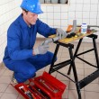 Stock Photo: Plumber adjusting pipe