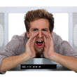 Stock Photo: A man shouting through a TV.