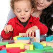 Woman with child and  blocks - Stock Photo