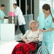 Stock Photo: Hospital nurse pushing elderly lady in wheelchair