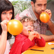 Family blowing balloons for a party — Stock Photo