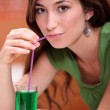Young woman dressed in green drinking a lemonade and mint cordial with a dr — Stock Photo #9059880