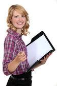 Blond secretary holding folder and pen — Stock Photo