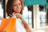 Smiling Metis woman carrying shopping bags — Stock Photo