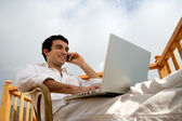 Man relaxing with laptop whilst sat in the garden — Stock fotografie