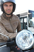 Man on a moped with a bus in the background — Stock Photo