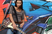 Female guitarist stood by graffiti — Stock Photo
