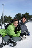 Young couple sat in snow — Stock Photo