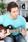 Hombre joven serio tocando su guitarra en casa — Foto de Stock