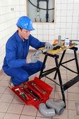 Plumber adjusting pipe — Stock Photo
