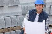 Construction worker standing next to pallets of concrete curb while looking — Stock Photo
