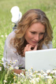 Relaxed woman lying in a field of daisies using her laptop — Stock Photo