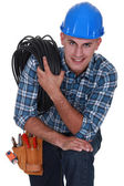 Tradesman carrying a cable coiled around his shoulder — Stock Photo