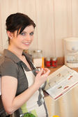 Woman eating a carrot and looking at a cookbook — Stock Photo