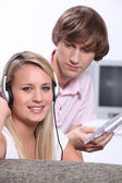 Teenagers listening to CD's on headphones — Stock Photo
