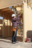 Contractor inspecting woodwork on house under construction — Stock Photo