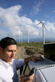 Man stood by wind farm taking readings — Stockfoto