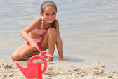 Little girl digging on the beach — Stock Photo