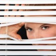Woman peering through blinds — Stock Photo #9060214