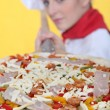 Female pizza cook putting a pizza in an oven — Stock Photo #9060403