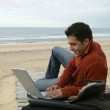 Man using his laptop at the beach — Stock Photo #9060667