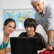 Students in class working on computer with teacher — Stock Photo