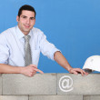 Businessman pointing at an at sign on a wall — Stock Photo