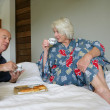 Senior couple in bathrobe sitting on a bed having breakfast — Stock Photo