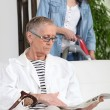Stock Photo: Young womvacuuming next to senior woman
