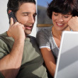 Couple in the sunshine with a laptop and phone — Stock Photo