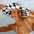 Woman wearing hat and bikini at the beach — Stock Photo