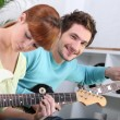 Stock Photo: A guitar teacher and his female student