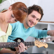 A guitar teacher and his female student — Stock Photo